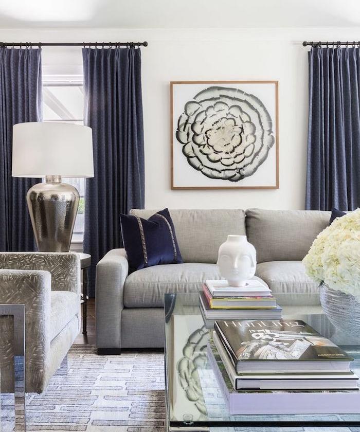 amenagement salon moderne avec canapé gris clair, rideaux bleu foncé, table basse en verre et fauteuil gris