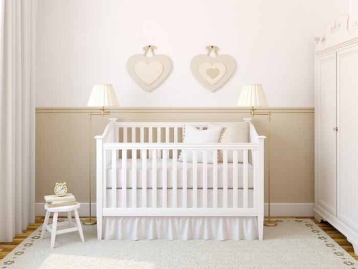 design intérieur classique dans la chambre bebe blanche avec déco pan beige et meubles de bois blancs