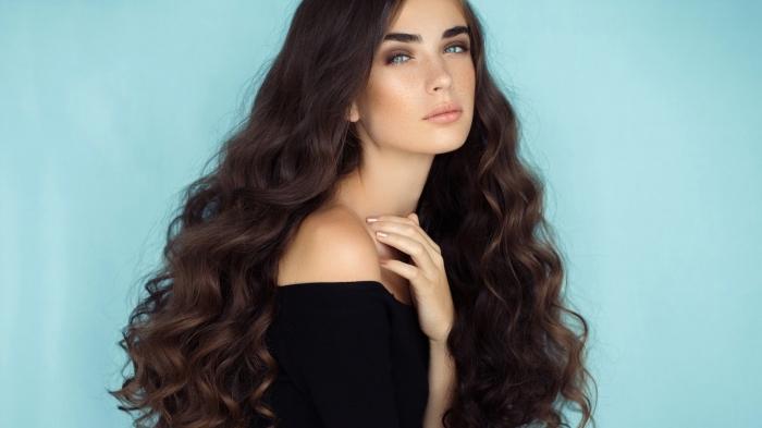 cheveux longs et sains naturellement bouclés et volumineux de couleur marron, maquillage pour yeux bleus avec lèvres nude