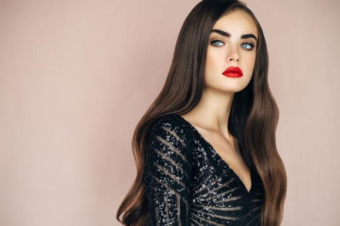 maquillage pour yeux bleus avec eye-liner et rouge à lèvres rouge matte, belle femme aux cheveux longs de couleur châtain foncé