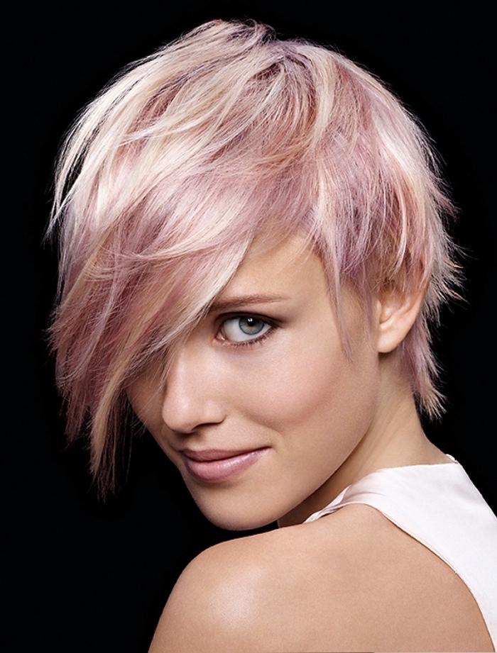 mèches rose pastel sur cheveux blonds courts avec frange hyper longue effilée à porter sur le côté pour un look déstructuré