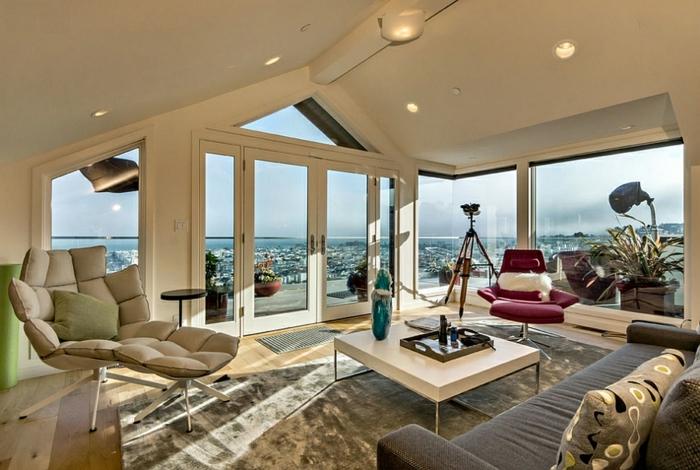 amenagement de combles créatif, table blanche carrée, tapis beige, grands fauteuils ergonomiques, canapé gris