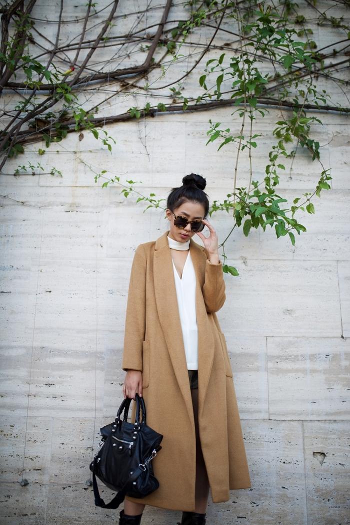 coiffure cheveux longs attachés en chignon haut décontracté, manteau camel femme long combiné avec chemise blanche et chocker blanc