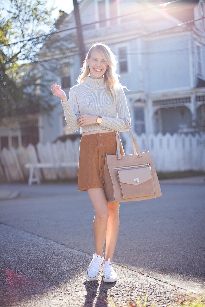 look casual chic en jupe courte à taille haute de nuance camel avec pull over crop gris et baskets blancs femme
