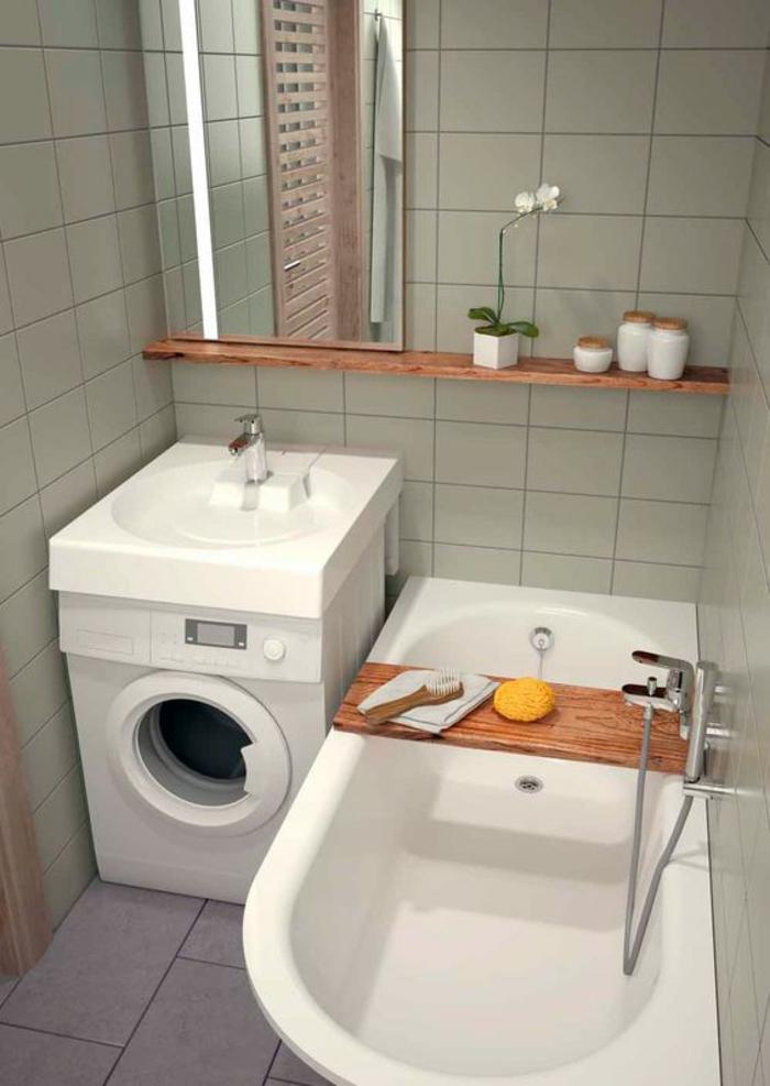 carrelage en gris clair, carrelage du sol avec des grandes dalles grises, amenagement salle de bain, étagère en marron, coin lave-linge, baignoire blanche, miroir rectangulaire