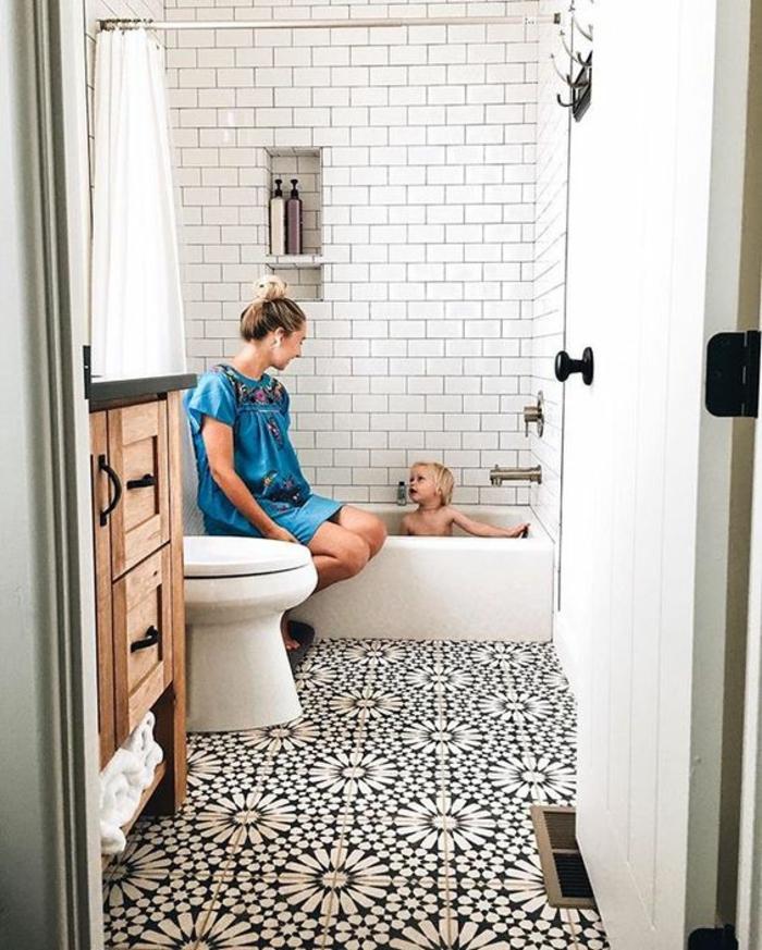 modele de salle de bain, carrelage en noir et blanc, aux motifs fleuris, mur dans la zone douche en briques blanches, meuble en bois avec des poignées noires métalliques, porte blanche