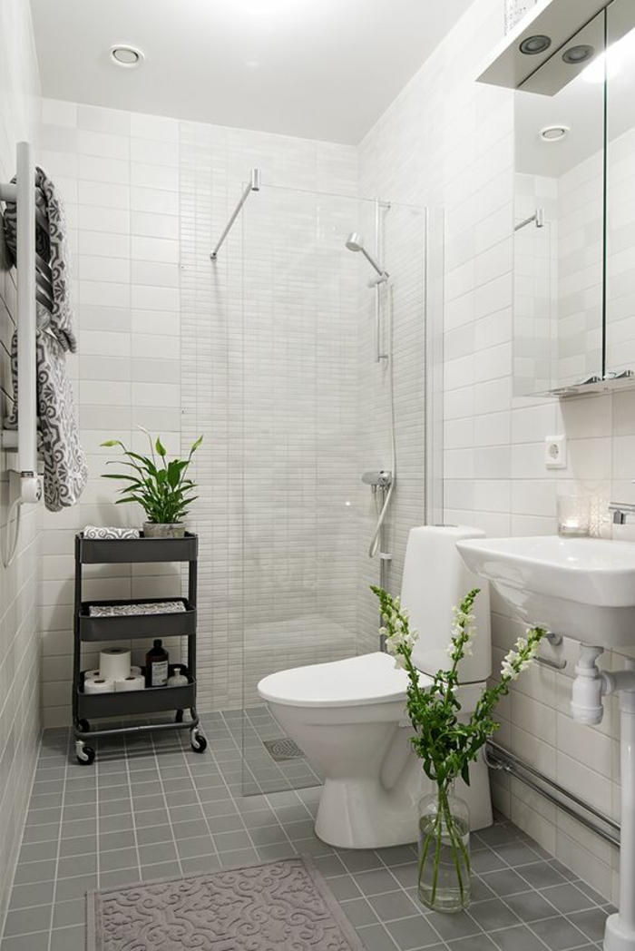 carrelage gris et murs en blanc, douche italienne de très petites dimensions, salle de bain 6m2, amenagemen salle de bain, meuble mibile en métal gris pastel, tapis rectangulaire rose poudré, meuble de rangement avec des portes en miroirs avec illumination de petits spots ronds