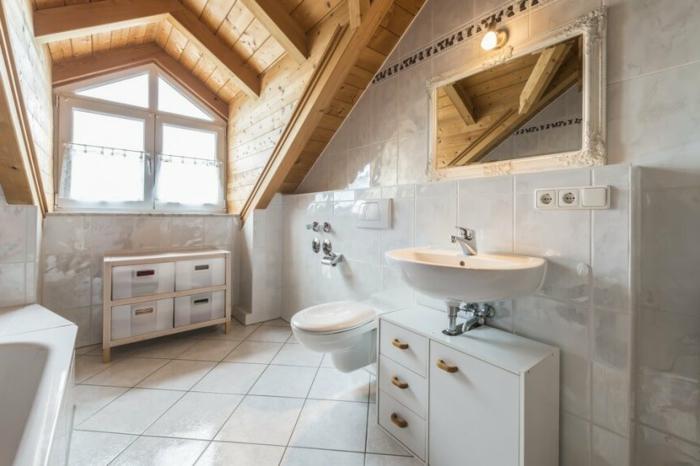 petit meuble sous vasque, vasque suspendue, plafond en bois, carrelage blanc, toilettes suspendus