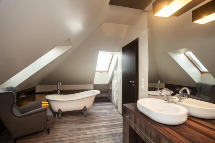 sol en planches de bois, grand miroir éclairé, meuble sous vasque en bois, vasque blanche, baignoire et fauteuil gris