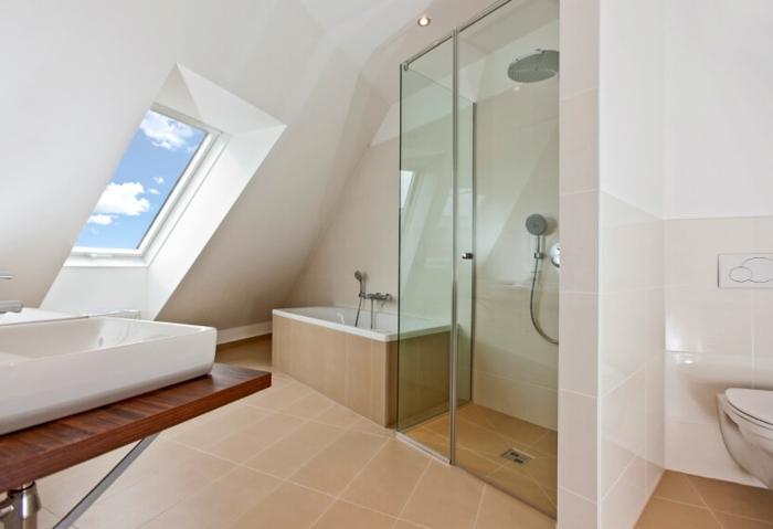 jolie salle d'eau mansardée, fenêtre en pente, cabine de douche en verre, carrelage de sol beige