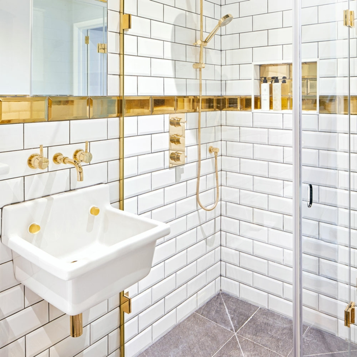 salle de bain 6m2, avec carrelage sol et mural en briques blanches effet poli, douche, évier et robinets en couleur or, accent en couleur or brillant qui passe sur la longueur du mur entier, carrelage sol en couleur prune, grand lavabo vintage