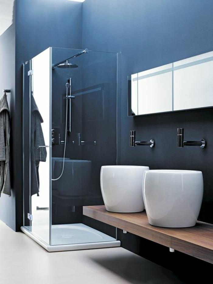 murs en bleu canard, douche italienne angulaire façon cube, carré, salle de bain 6m2, amenagement salle de bain, deux lavabos ronds et hauts sur une surface imitation bois couleur marron clair
