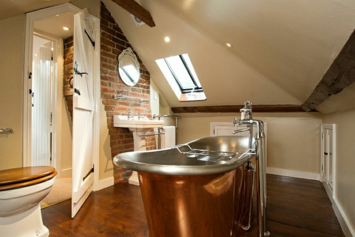 murs en briques rouges, baignoire en fonte, sol en bois, petite fenêtre en pente