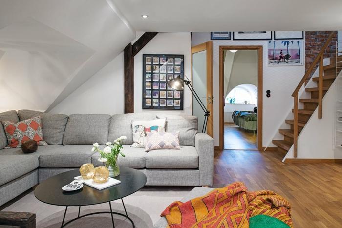 escalier en bois et blanc, sol stratifié, table basse ovale, canapé d'angle gris, déco poutre apparente