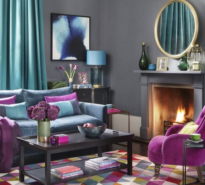 murs peinture gris anthracite avec cheminée design, rideaux et canapé bleu, table basse marron foncé, coussins et fauteuil fuchsia, tapis à triangles colorés