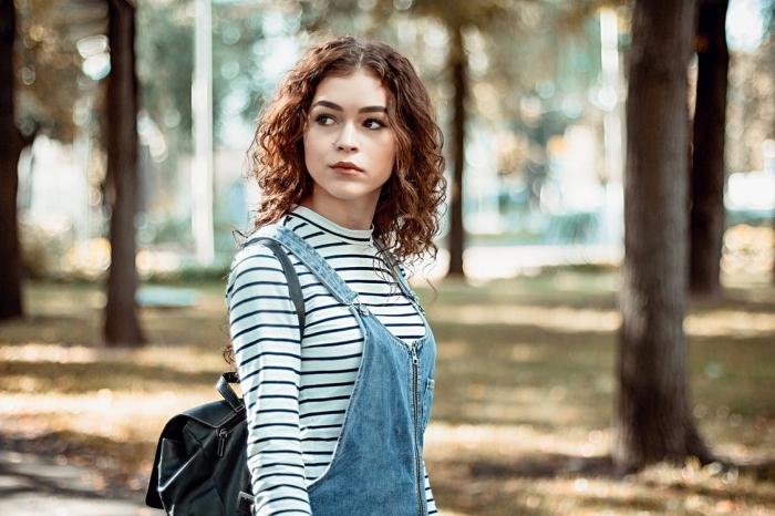 comment porter la salopette en denim clair avec blouse rayée en blanc noir et sac à dos cuir noir, couleur cheveux marron longs et bouclés