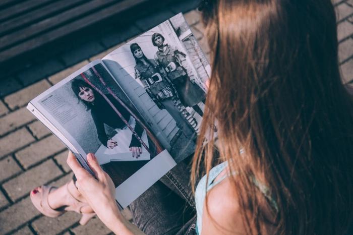 jeune fille aux cheveux cuivré de base châtain foncé, tenue casual en jeans foncé et sandales beige à talons hautes