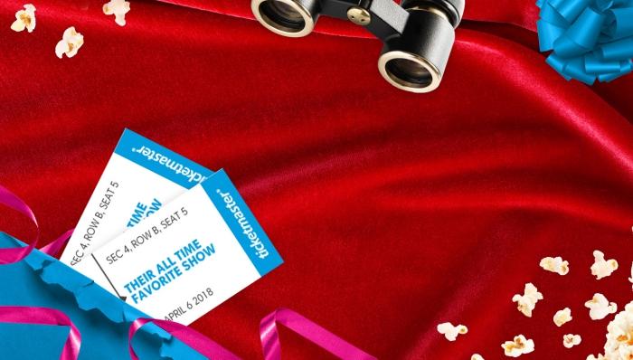 billets de spectacle sur une nappe rouge couverte de popcorns, modèle de binocles et emballage de cadeau en papier bleu