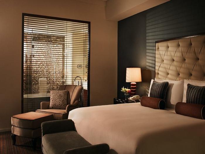 decoration murale avec une tête de lit, lit taupe, fauteuil et tabouret beige, salle de bain et chambre