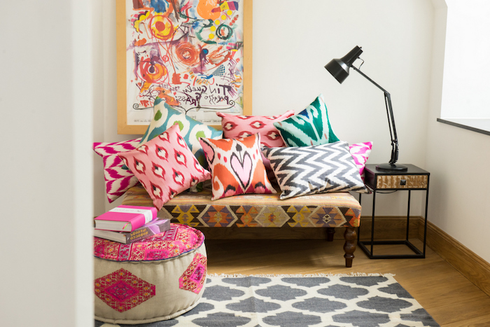 tapis nuance gris souris, sol en parquet bois, pouf à motifs orientaux et coussins décoratifs orientaux sur un petit banc, deco murale art abstrait coin boheme chic