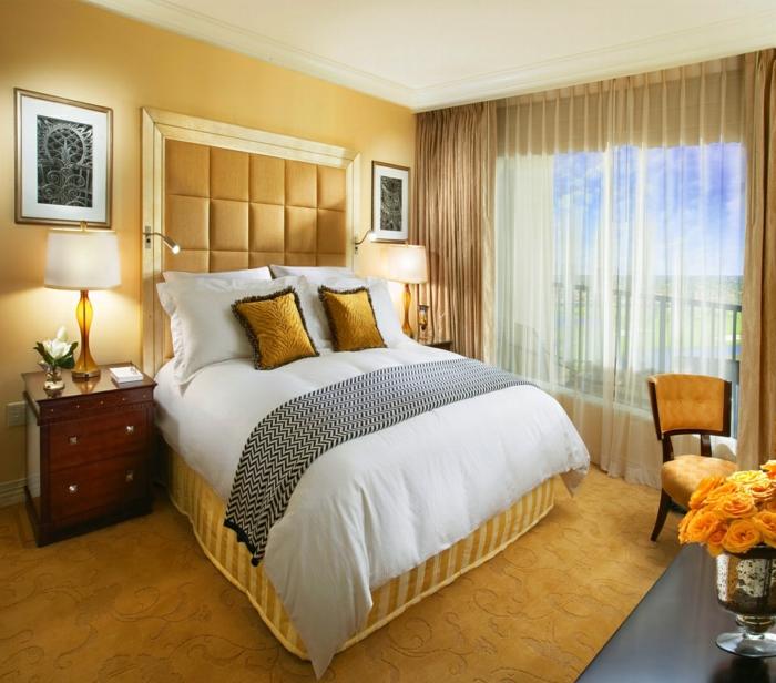 rideaux transparents, lit avec deux coussins jaunes ocre, tête de lit capionnée jaune
