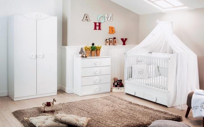 aménagement de la chambre bébé mixte aux murs beige avec fenêtres de plafond et parquet de bois clair