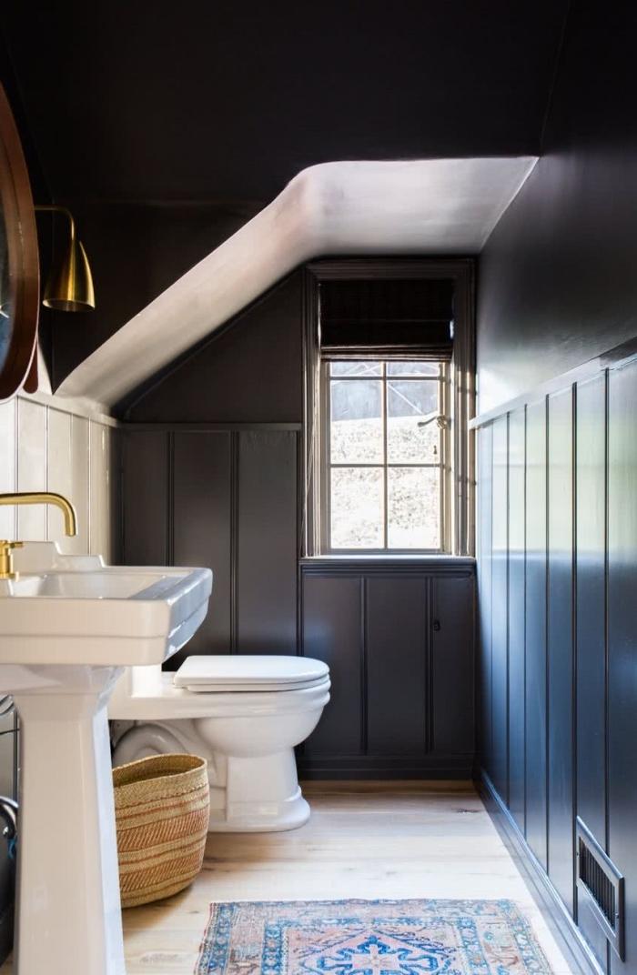 meuble salle de bain sous pentes aux murs et plafond noir avec revêtement de plancher en bois clair et tapis à motifs ethniques