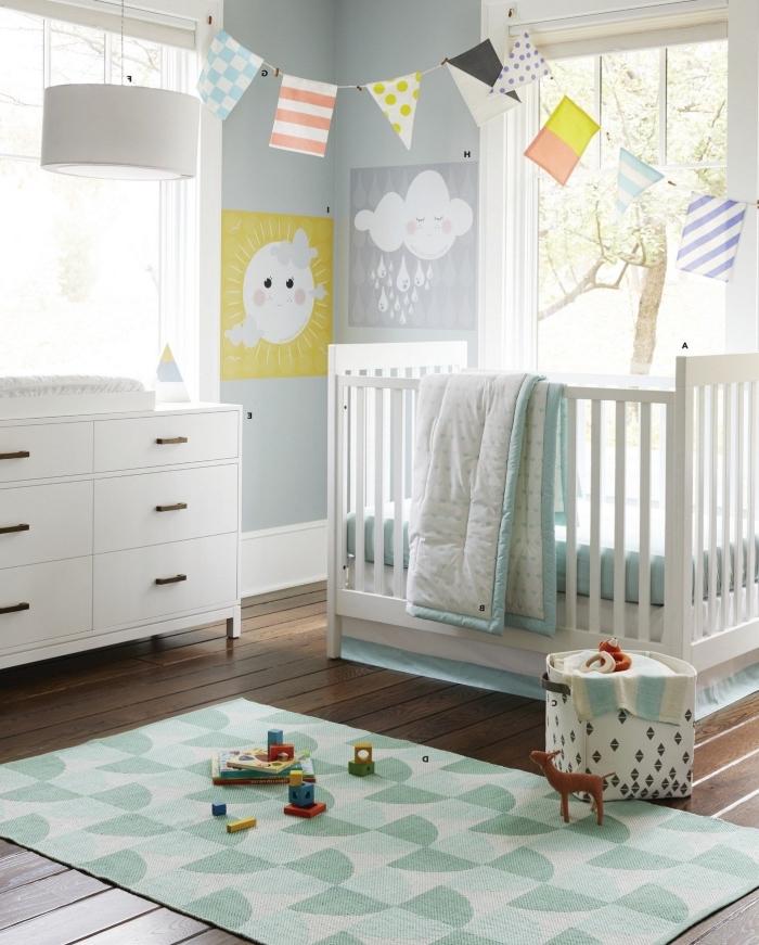 objets diy décoratifs dans la chambre bébé aux murs bleu pastel, meubles de bois peints en blanc sur un parquet de bois foncé