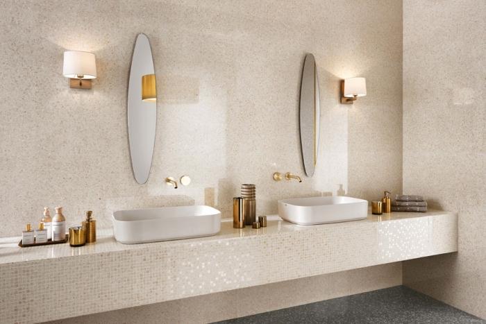 deco salle de bain en nuances beige et blanche, revêtement mural en carrelage beige, modèle de miroir oval et accessoires de bains cuivrés