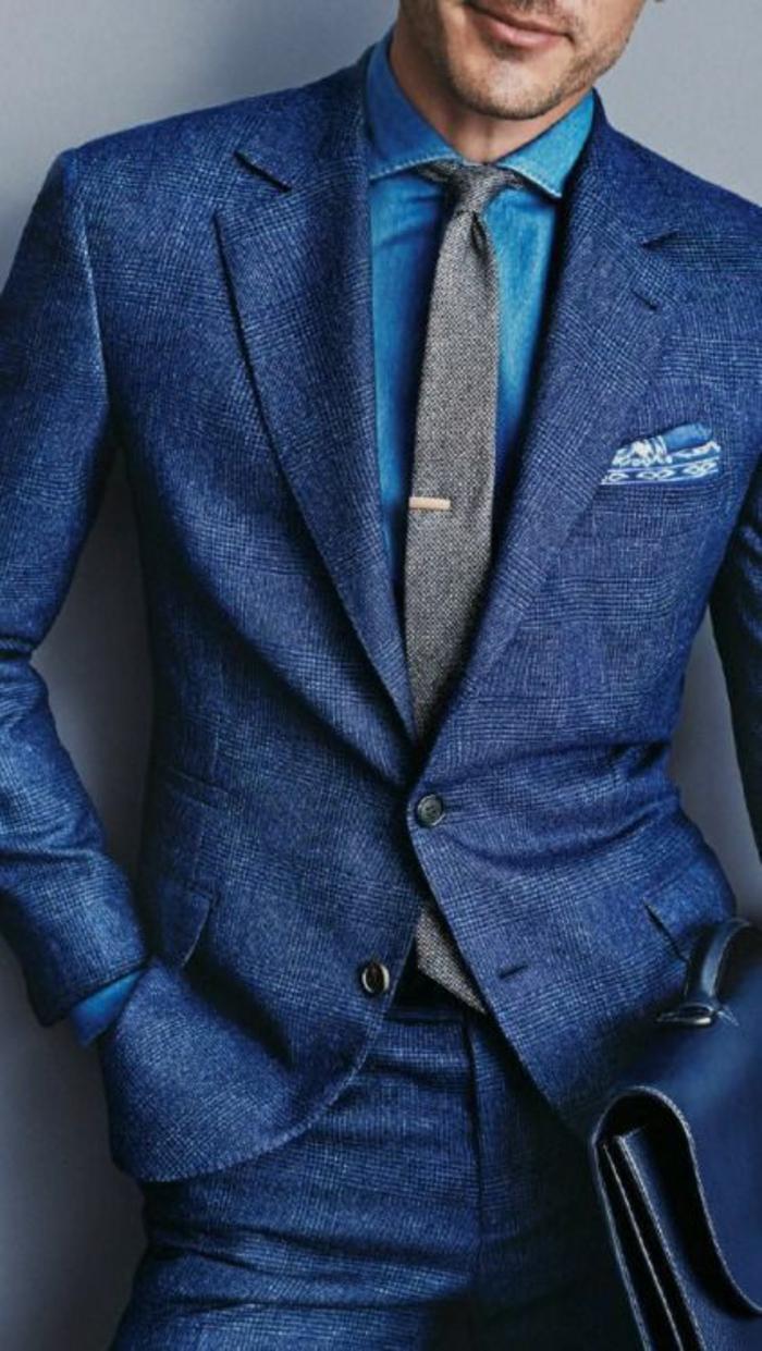 costume bleu roi, cravate grise avec pince en métal jaune, sac pochette pour les documents en bleu roi avec poignée, costume en laine Canali