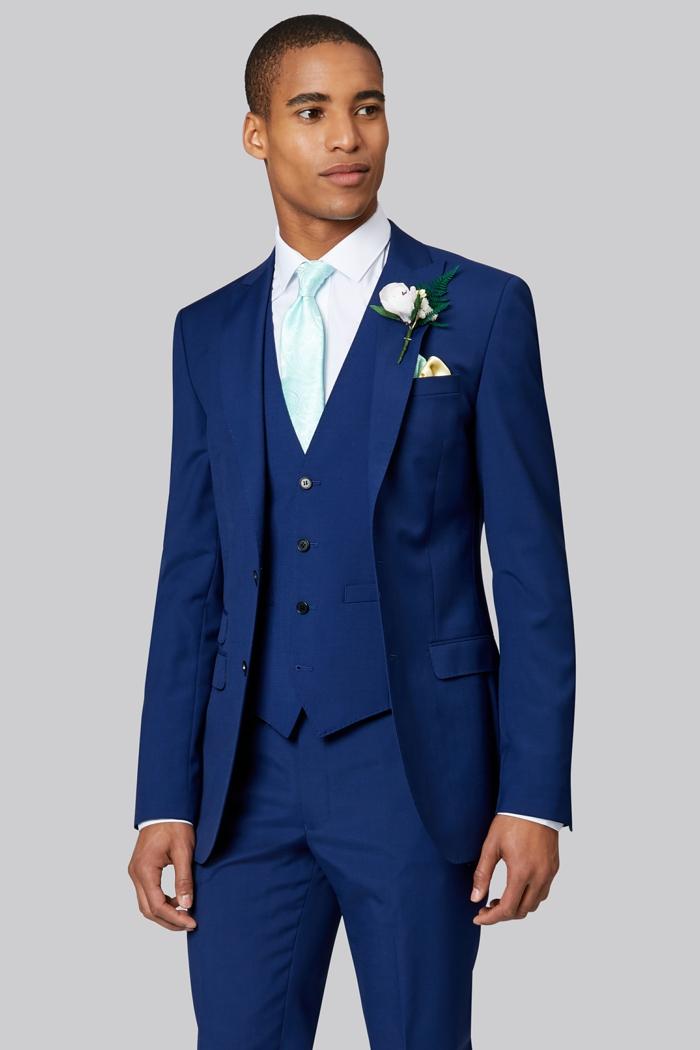 veste de costume homme, chemise blanche, gilet en bleu roi, cravate en soie vert menthe, boutonnière ornée d'une rose blanche