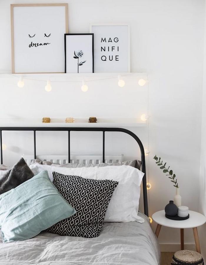 modele de tete de lit a faire soi meme en guirlande lumineuse boule, lit metallique noir, linge de lit blanc et coussins décoratifs en noir, blanc et vert clair, deco murale noir et blanc