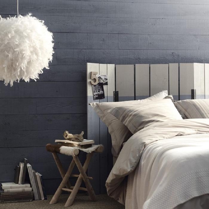 chambre à coucher de style rustique revêtue de lambris gris anthracite avec une tete de lit en palette peinte en blanc et gris