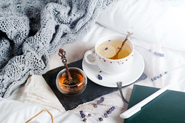 lit cocooning avec un plad tricoté, des tasses avec des boissons chaudes