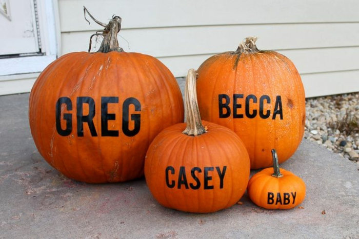 photo anonce grossesse, les noms des quatre membres de la famille écrits sur quatre citrouilles
