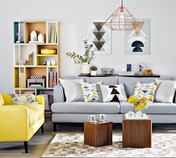 mur décoré de peinture gris clair, canapé gris, fauteuil jaune, tables basses en cube de bois, etagere rangement en bois, suspension originale