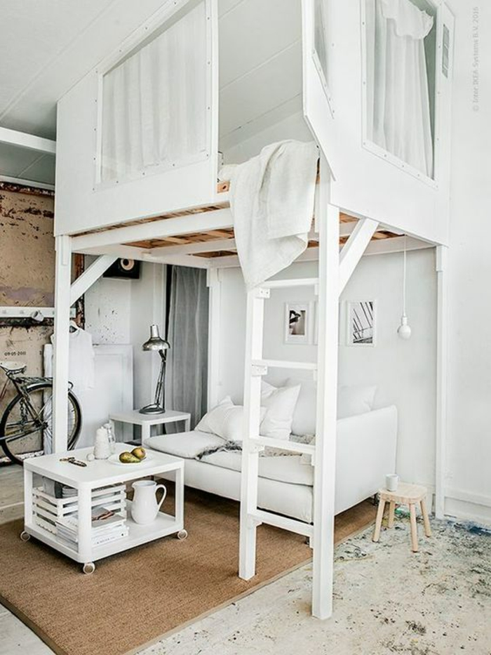 amenager studio 15m2, table fabriquée soi-même en palettes peinte en blanc, superposition des espaces lit et canapé en dessous, vélo parqué dans l'entrée, échelle blanche, canapé blanc, luminaire en métal gris, des lithographies au mur