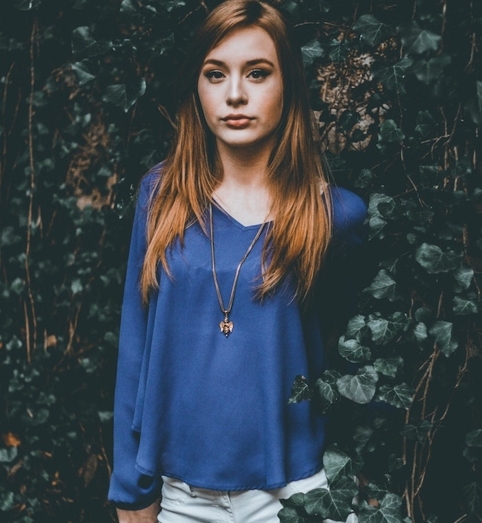 coupe de cheveux fille, cheveux longs en dégradé avec coloration chatain cuivré, tenue chemise bleue, pantalon blanc
