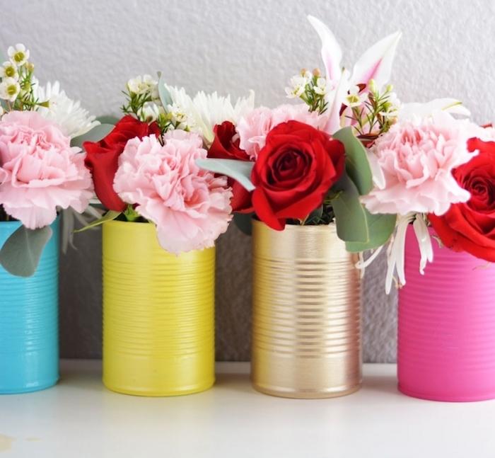 exemple d activité manuelle pour ado, des boites de conserve décorées de peinture jaune rose, or et bleu avec des bouquets de fleurs à l intérieur