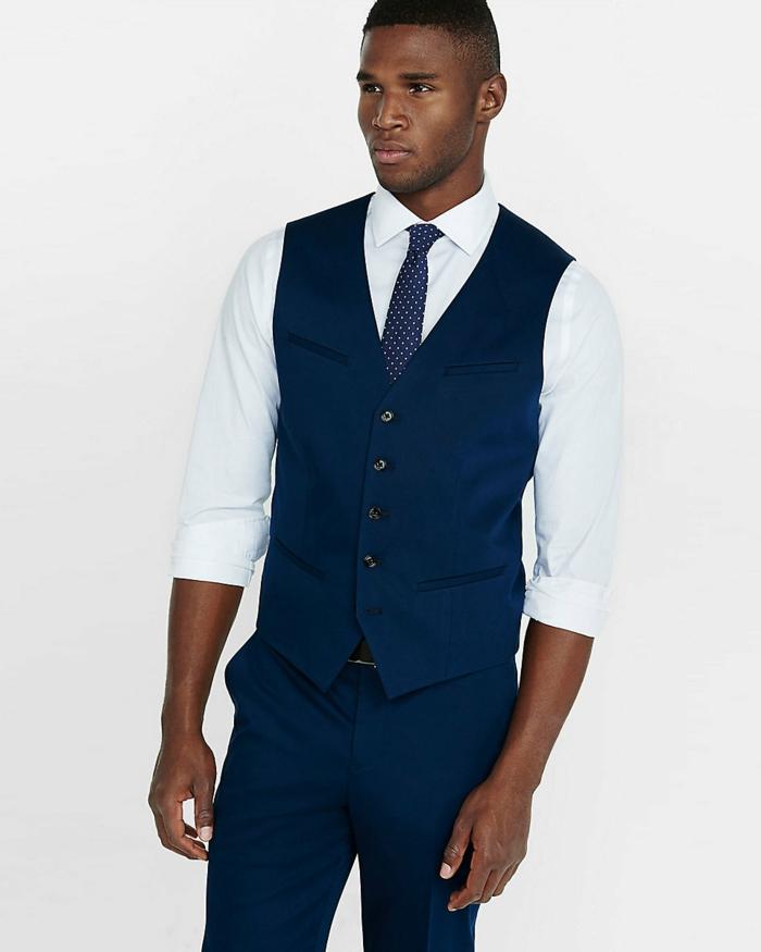 look avec un costard mariage, cravate en bleu roi avec des petits pois blancs, chemise blanche avec des manches retroussées, pantalon sur le corps