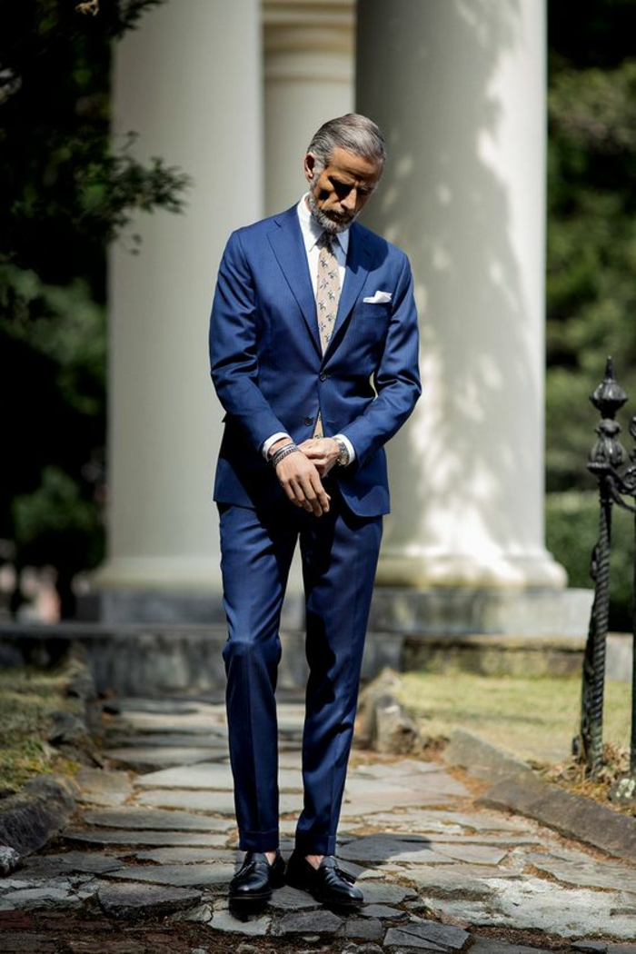 homme mur avec un costume hugo boss, costume bleu roi, chemise blanche, cravate avec des motifs colorés en nuances pastels, chaussures noires en laque, mouchoir de poche blanc