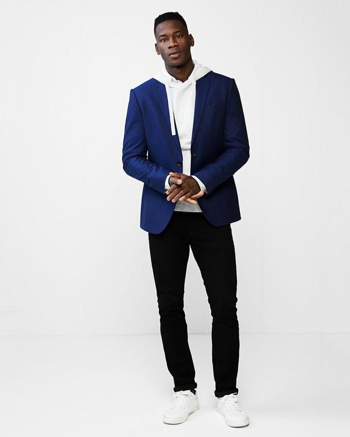 veste de costume homme, sweater blanc avec des ficelles pour le capuche, pantalon noir moulant, baskets blanches