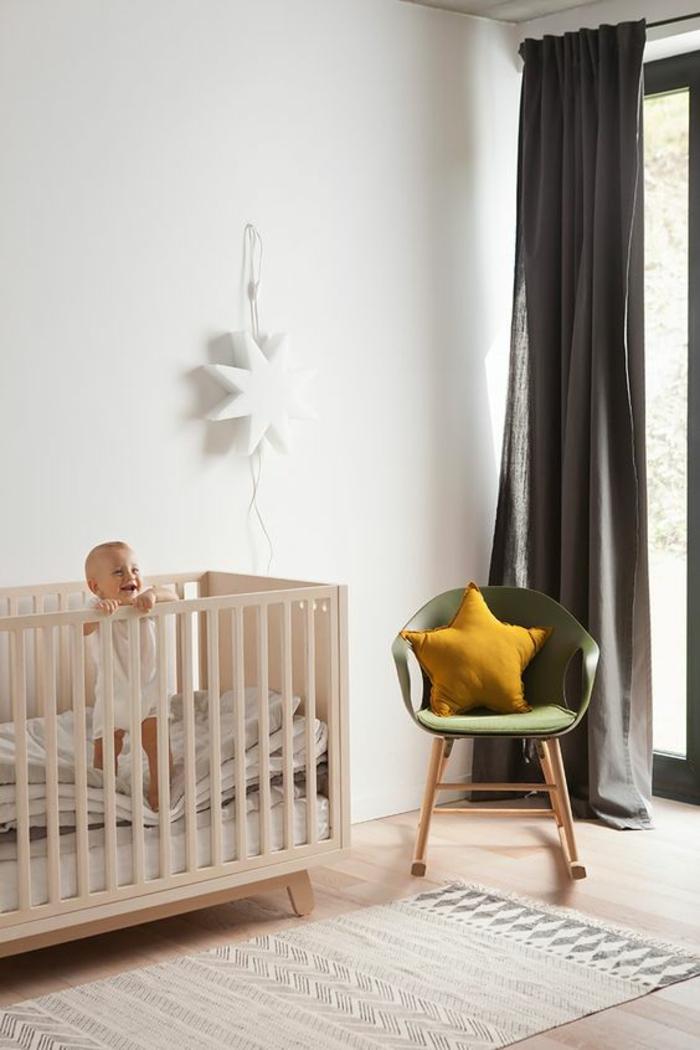 décoration chambre bébé fille, lit rose, fauteuil en vert réséda, une grande étoile blanche au mur, tapis en rose pastel et en gris, rideaux gris perle