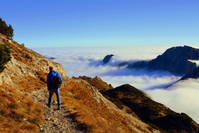 paysage montagneux, homme qui marche sur un petit chemin qui va en zig-zague dans la montagne, touriste qui a surpassé le niveau des nuages