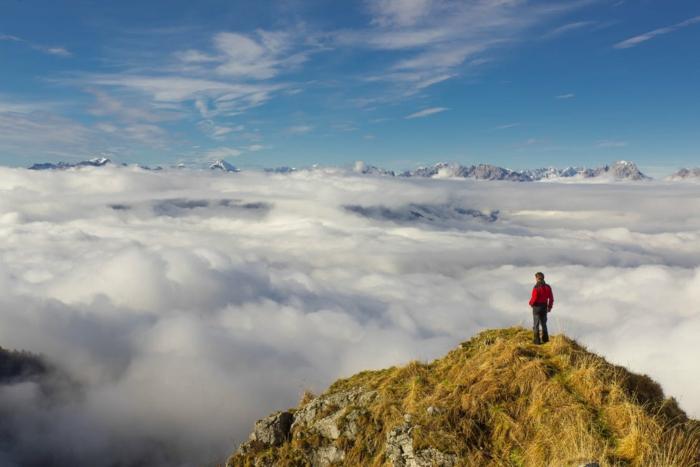 des nuages blancs qui ressemblent a de la vapeur qui s'élève vers le ciel, homme avec veste rouge monté sur une roche qui contemple les nuages