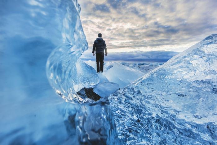 fond ecran paysage, paysage glacier, homme qui marche sur la glace prudemment, ciel couleur pourpre et rose, paysage paradisiaque