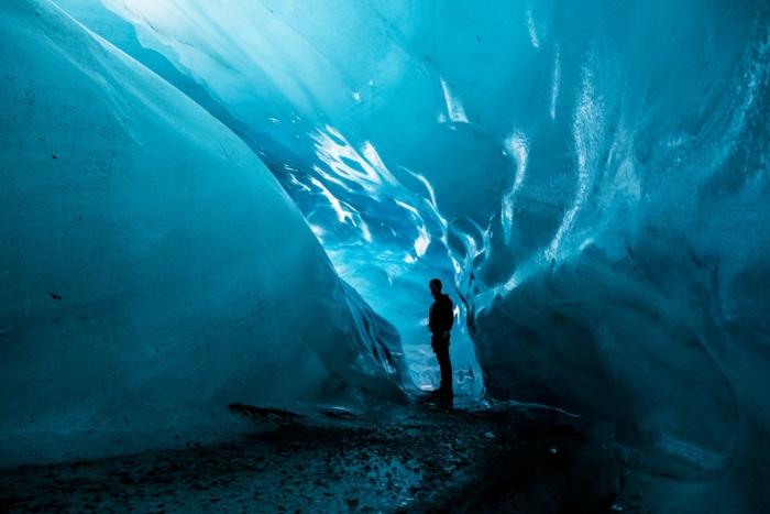 un homme dans une grotte de glace, beau paysage paradisiaque, ambiance de tranquillité et de paix, lumière douce qui illumine la glace