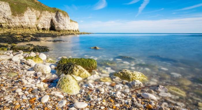 une plage avec des beaux coquillages blancs, iles paradisiaques, paysage mer, horizon ensoleillé, rochers blancs couverts de vert, eaux bleues transparentes