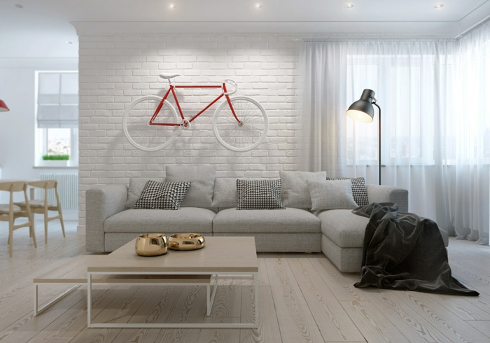 amenagement salon, parquet en bois clair, mur en briques blanches, deux tables en matière PVC et en métal blanc, luminaire sur pied en métal noir, rideaux semi-transparents blancs, plafond blanc parsemé de petits spots