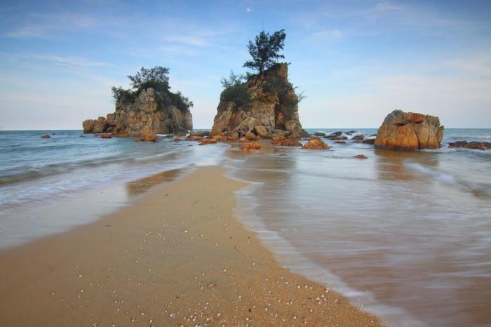 fond ecran paysage,trois rochers couverts de buissons verts, sable beige, ciel bleu avec des nuages minuscules transparents
